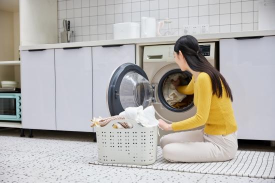 摄图网_501714118_banner_家庭主妇居家整理脏衣篮洗衣服(企业商用)